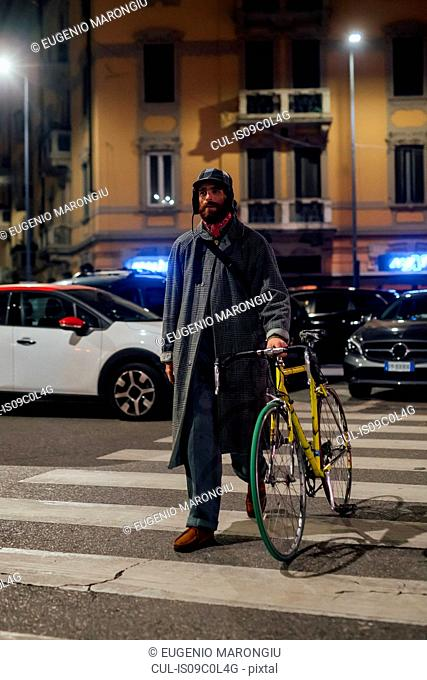 Bearded young man walking on pedestrian crossing with bicycle
