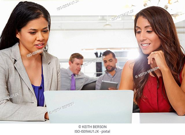 Two businesswomen sitting at desk, looking at laptop