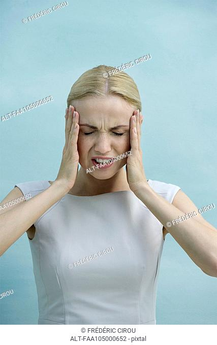 Woman holding head in frustration