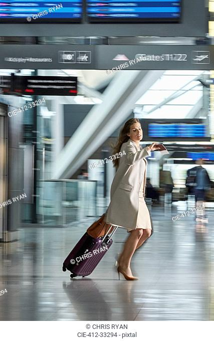 Businesswoman rushing pulling suitcase and checking the time in airport concourse