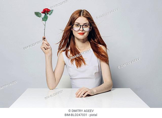 Caucasian woman sitting at windy table holding rose