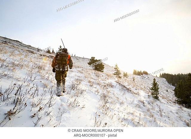 A male hunter at sunrise in the snow