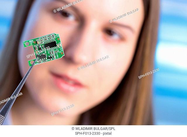 Female electrical engineer holding micro chip in tweezers