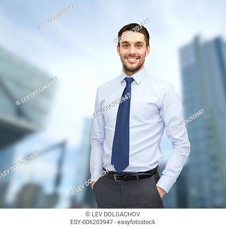 business and people concept - smiling young and handsome businessman over business centre background
