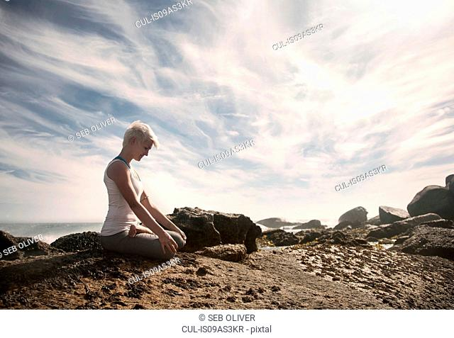 Woman practising yoga by ocean, Cape Town, South Africa