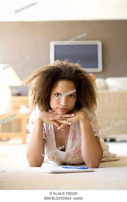 African woman on floor with note pad