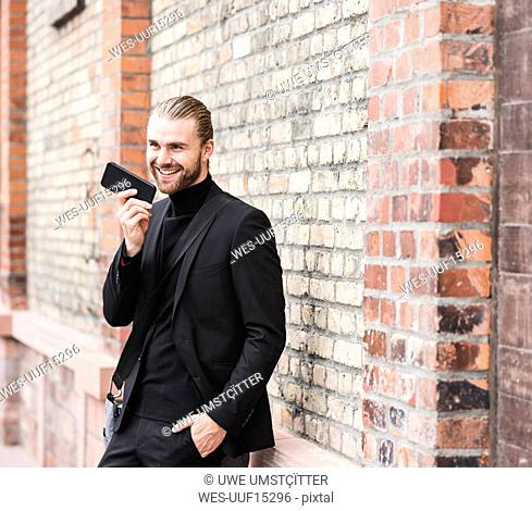 Smiling fashionable young man standing at brick wall using cell phone