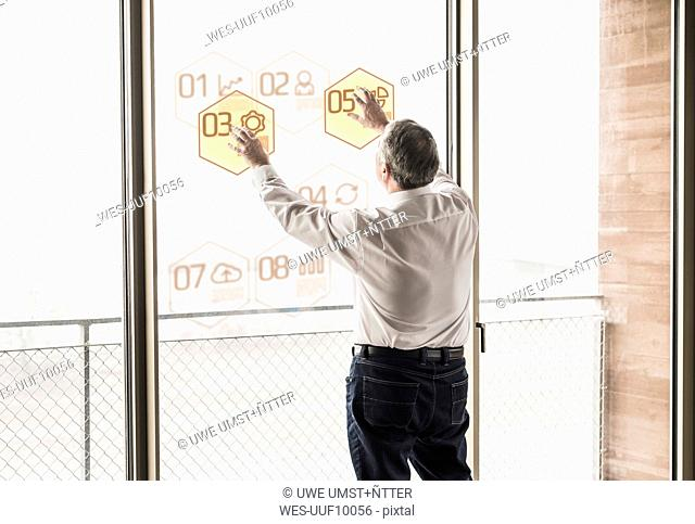 Businessman touching windowpane with data in office