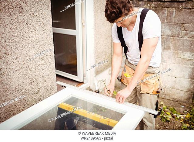 carpenters hands measuring a door frame