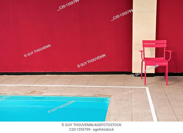 Pink metal chair and blue water of indoor swimming pool Best Western Hotel Reims Marne 51 France