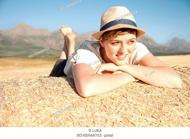 Woman lying on stomach on haystack