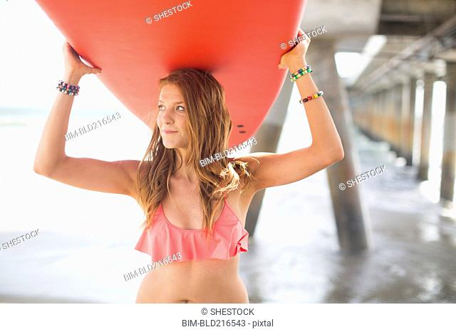 Woman carrying surfboard under boardwalk on beach