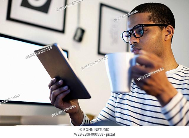 Young creative man with mini tablet having coffee break in his home office