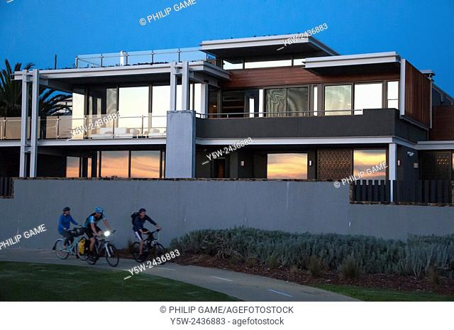 Cyclists passing a multi-million dollar luxury seaside home on Brighton's 'Golden Mile', Melbourne, Australia