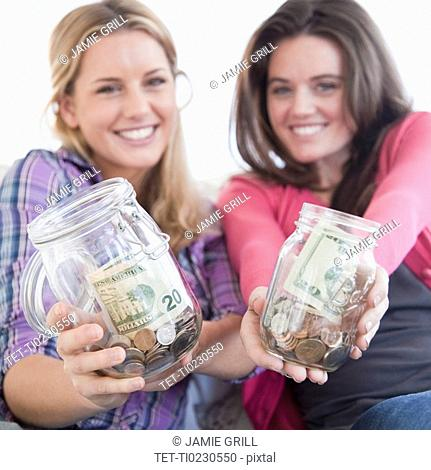 Woman holding jars of money
