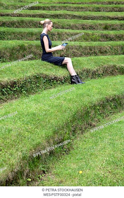 Italy, Alto Adige, Lana, woman sitting on grass-covered steps of natural open air theater using tablet