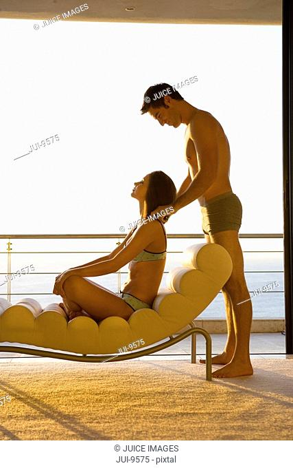 Young man standing by woman sitting on chaise lounge by balcony, side view