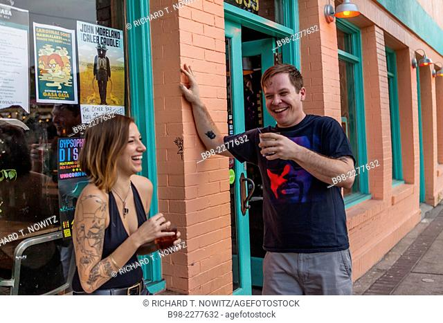 A couple enjoy a drink on the sidewalk on Ferret St, in the Garden District of New Orleans