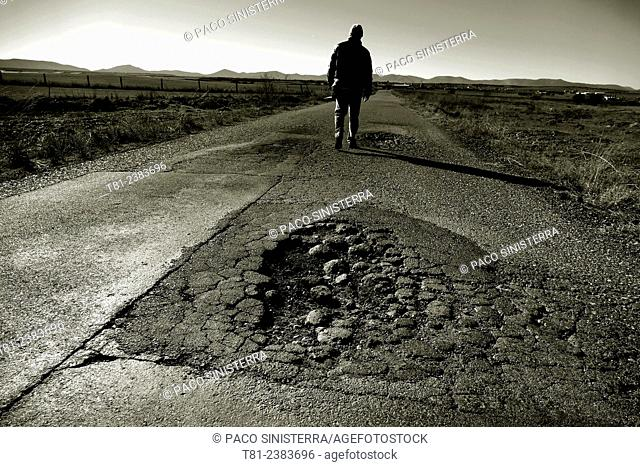Man walking along road broken in La Mancha, Toledo