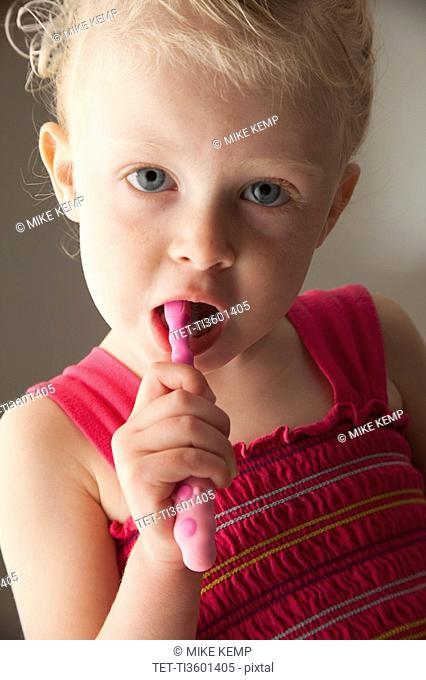 Cute young girl brushing her teeth