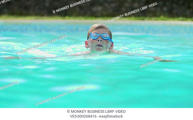 Young boy in pool swimming towards camera wearing goggles.Shot on Sony FS700 in PAL format at a frame rate of 25fps