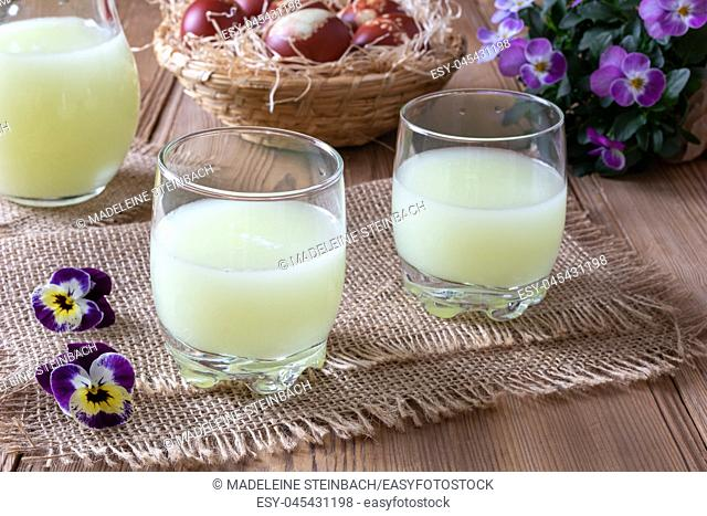 Two glasses of fresh whey with pansy flowers in the background