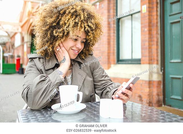 Woman sitting outdoors at a coffee shop with a drink. She is using a smart phone