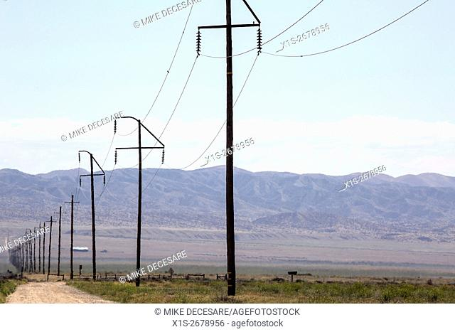 A straight line of power poles and power lines disappears into the distance in a remote landscape in Central California