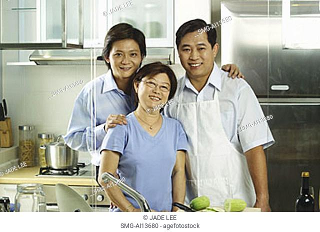Family with adult offspring, standing in kitchen