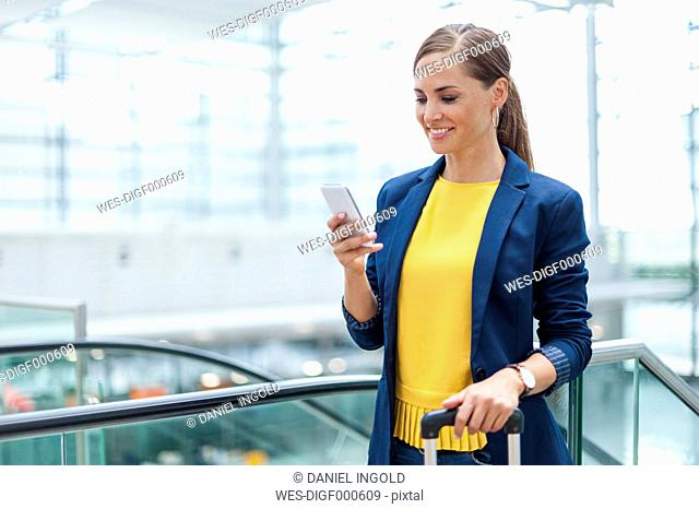 Smiling woman at a station looking on cell phone