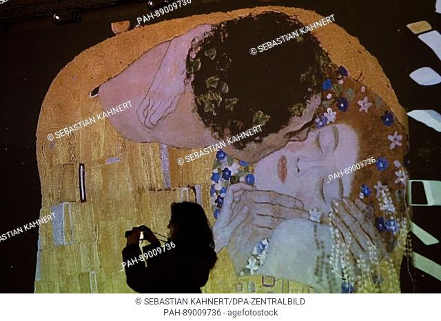 A woman takes pictures in front of a video projection in the exhibition 'Monet 2 Klimt' in Dresden, Germany, 14 March 2017