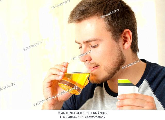 Man drinking an orange liquid medicine in a house interior