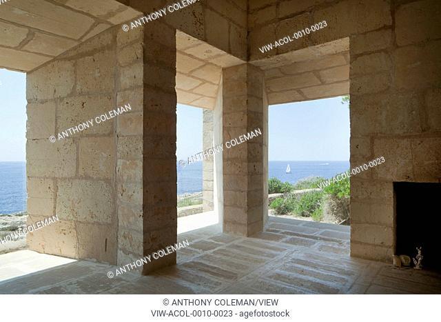 Can Lis, Mallorca, Spain. Architect: Utzon, Jorn, 1971. Living Room, frameless windows, view of sea. Fire place