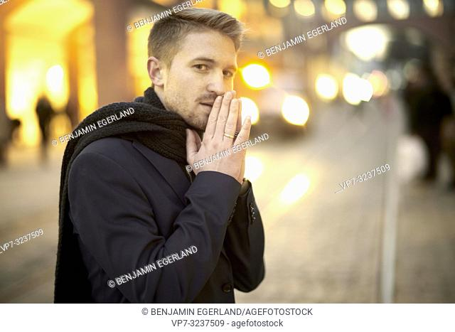 man with folded hands at street at evening, in city Munich, Germany