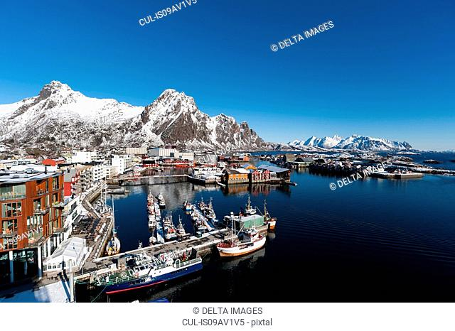 Elevated view of harbour and snow capped mountains, Svolvaer, Lofoten Islands, Norway