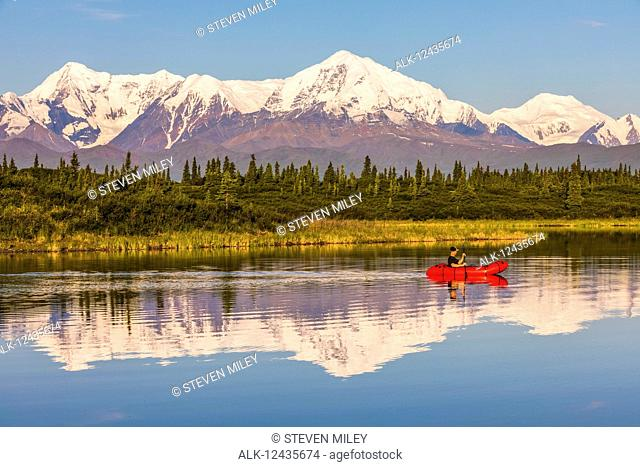 A man paddles across Donnelly Lake in a pack raft with Mt. Moffit and the Alaska Range reflecting on the water; Alaska, United States of America