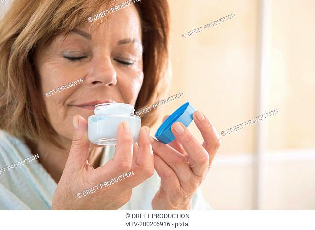 Senior woman smelling sun cream, Munich, Bavaria, Germany