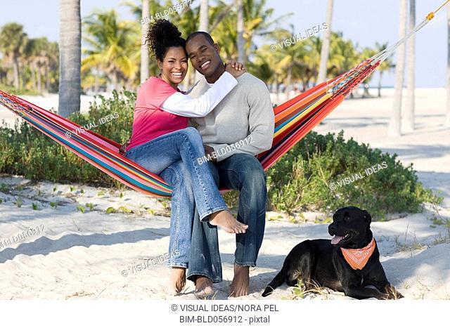 Hispanic couple hugging in hammock