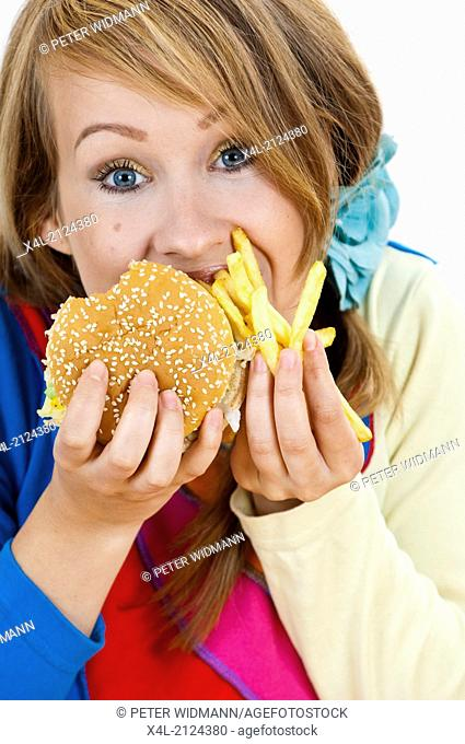 woman stuffing herself with big mac and French fries (model-released)