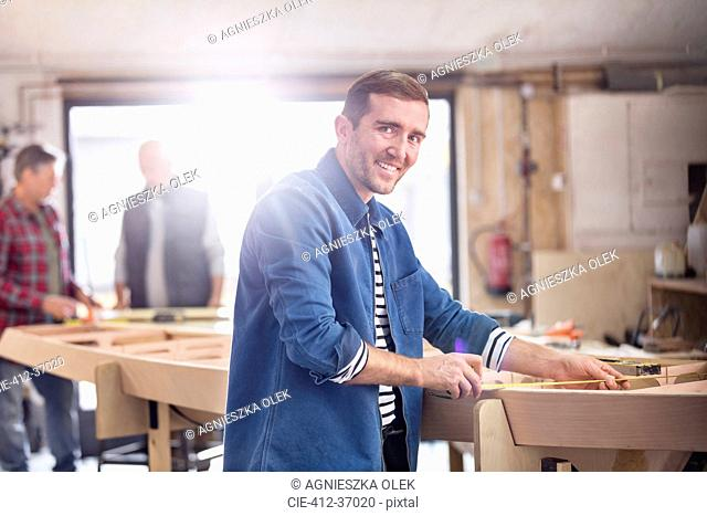 Portrait smiling male carpenter measuring wood on boat in workshop