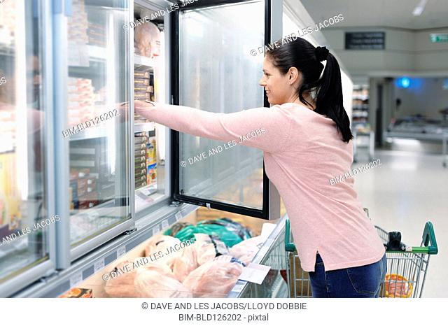 Hispanic woman reaching in frozen food case in supermarket