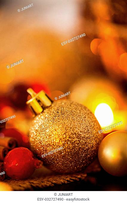 Warm gold and red Christmas candlelight background with burning tea lights amongst random gold and red baubles in a warm glowing light with copyspace