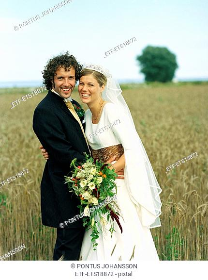 Scandinavia, Sweden, Oland, Bride and groom standing in field, smiling, portrait