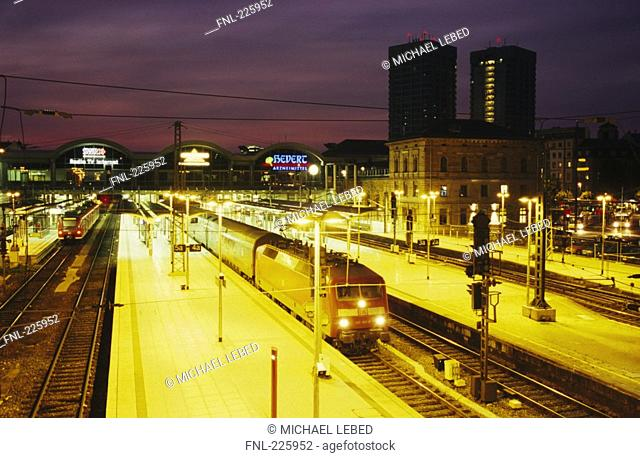 Trains at station lit up at dusk, Mainz, Germany