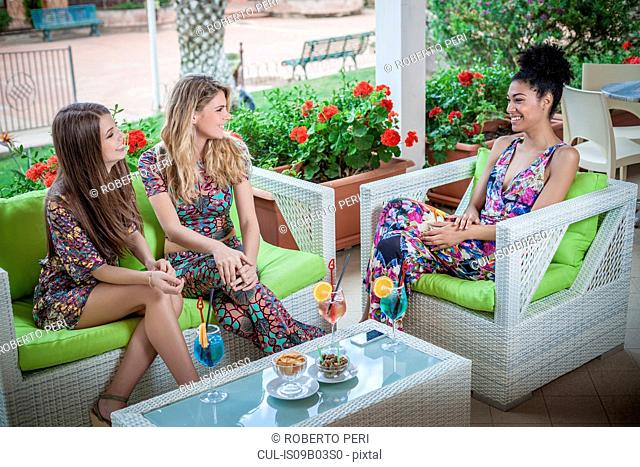 Three young women relaxing on apartment patio talking, Costa Rei, Sardinia, Italy