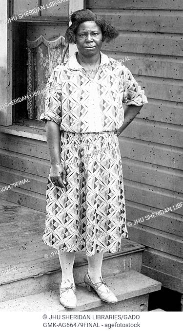 Full length portrait of African American woman, standing on a porch, one hand on her hip, wearing a patterned dress, with a serious facial expression, 1930