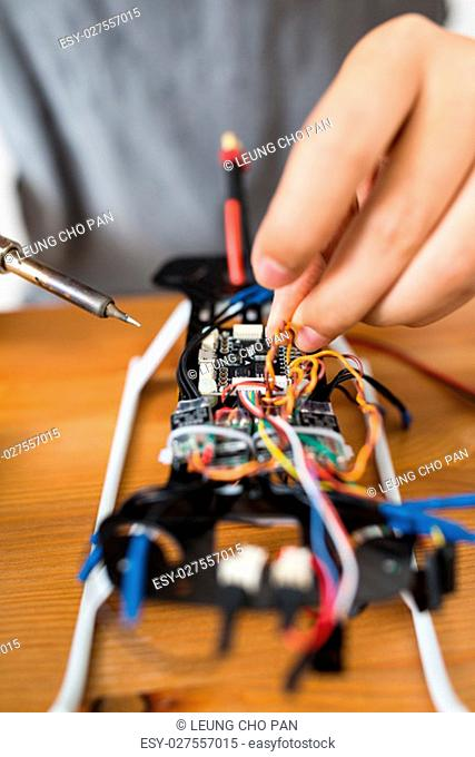 Man welding parts on drone body
