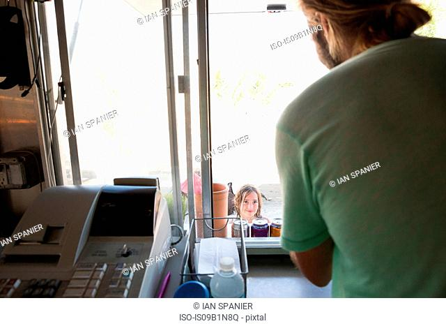 Man in fast food trailer, leaning through hatch, taking customer's order, rear view