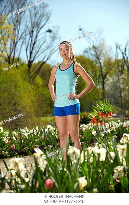 Sportliche Frau steht in einem Park im Frühling