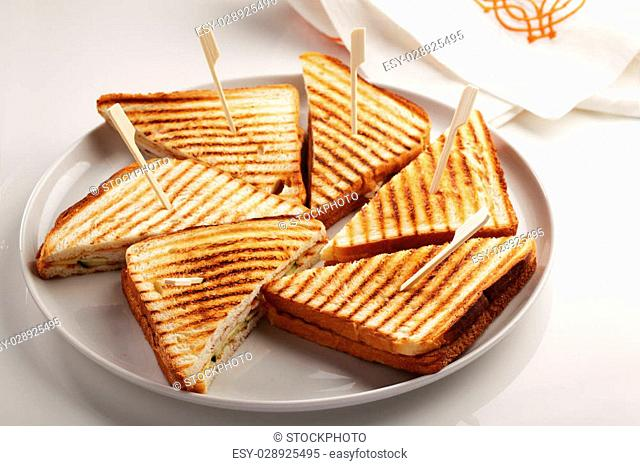 Sandwiches with chicken meat, cheese, cucumber, and grilled toasts on a white dish